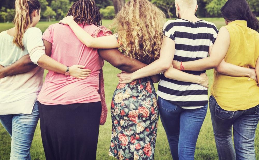 5 donne camminano abbracciate su un prato