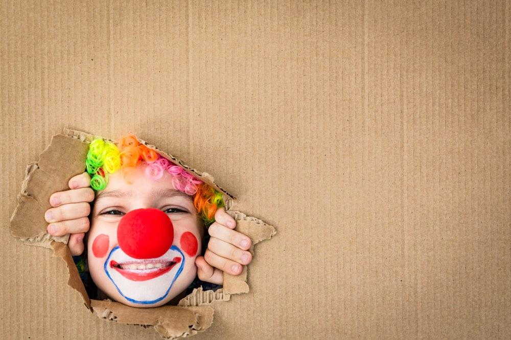 Bambino vestito da clown spunta da un cartone col viso