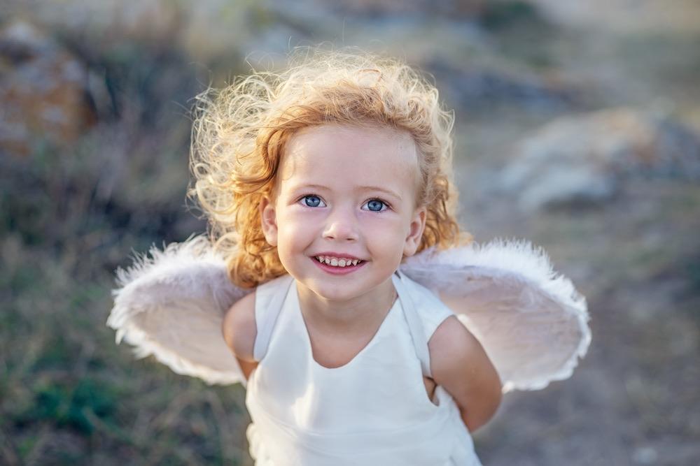 Bambina con occhi azzurri e ricciooli biondi con ali da angelo