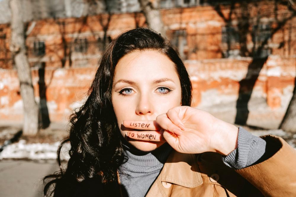 Ragazza con due dita sulla bocca con scritta Listen to women