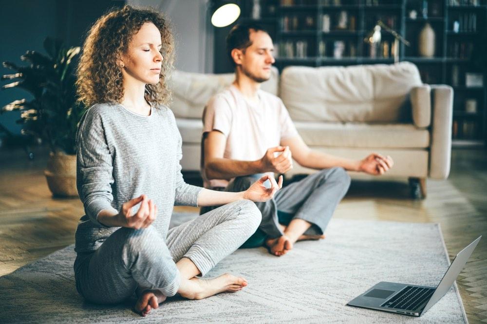 Coppia pratica meditazione nel salotto davanti al computer
