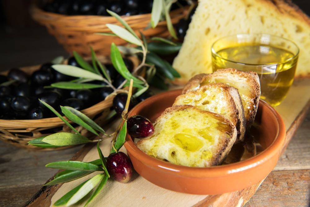 Fette di pane e olio EVO con olive, dentro piatto di coccio