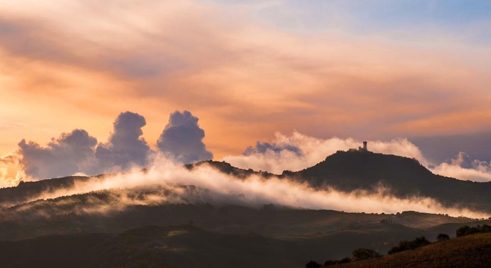 La Rocca di Radicofani dalla Via Francigena, all'alba con nebbia e nuvole in dissolvenza