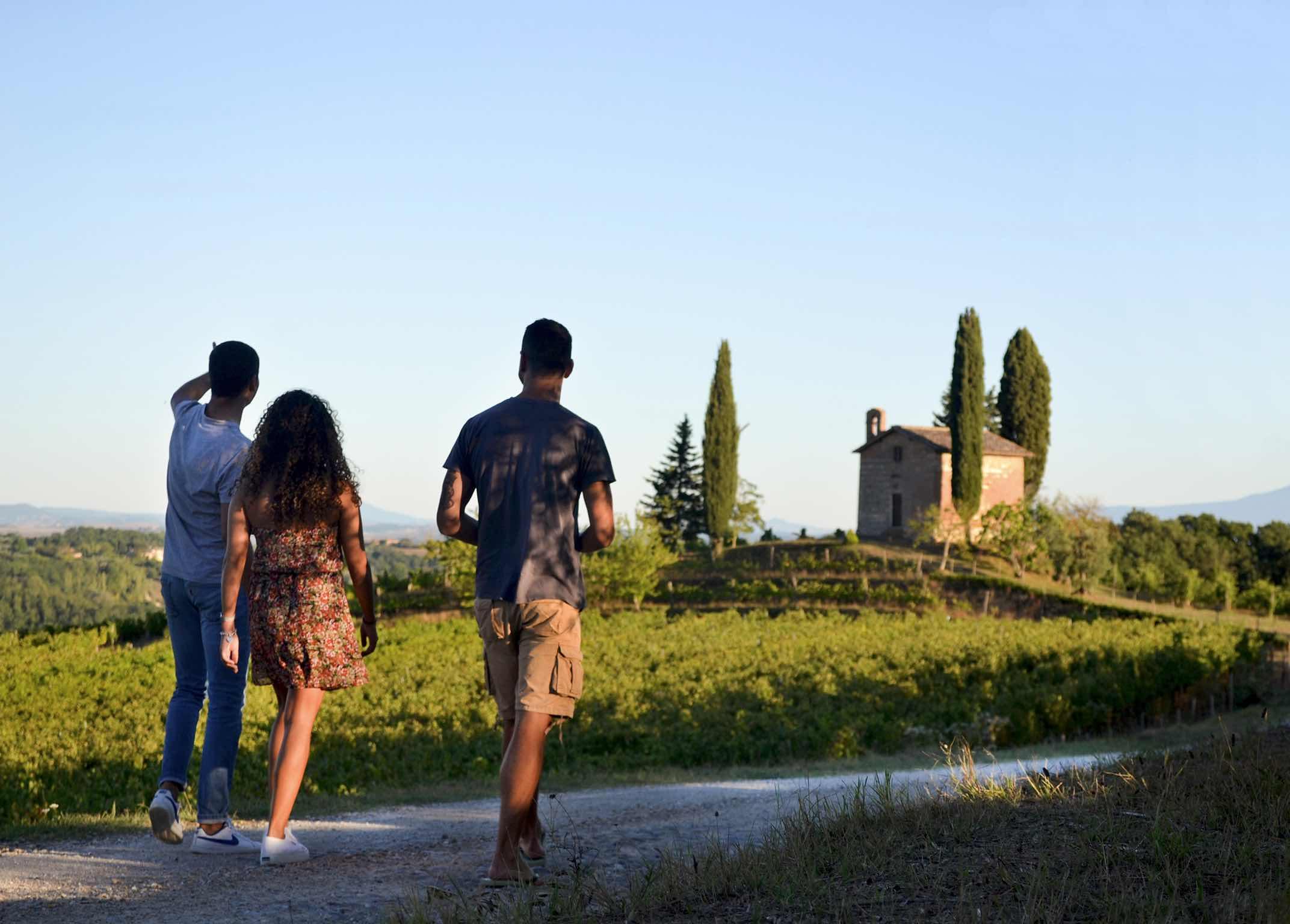 Tre persone camminano nella Tenuta di San Giorgio a Lapi con vista sui campi e sulla chiesa