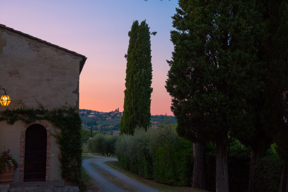 Veduta del borgo di Sinalunga al tramonto da una tipica stradina toscana di campagna