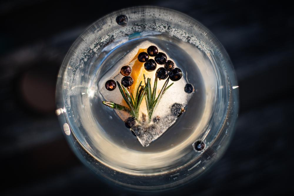 Bicchiere di gin con ghiaccio, arancia e bacche di ginepro
