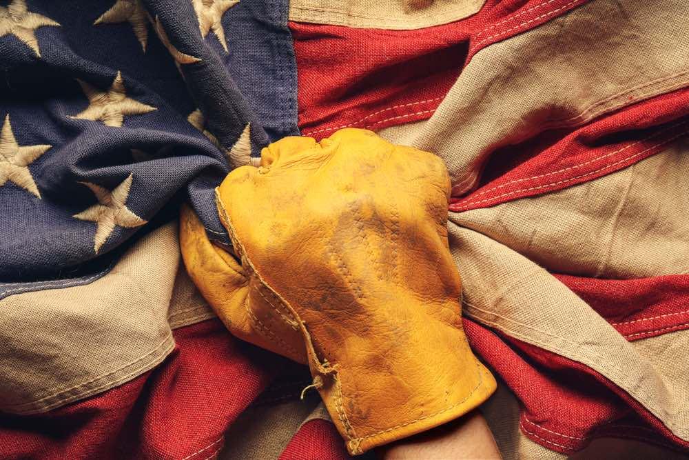 Bandiera americana stretta in un pugno con un guanto da operaio