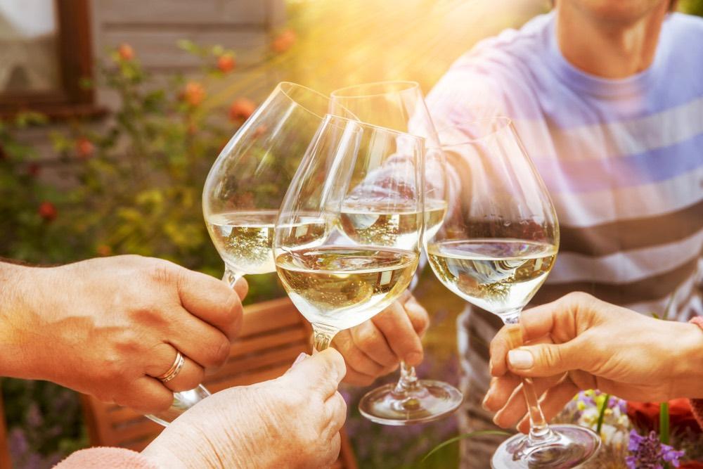 Persone brindano cn calici di vino bianco