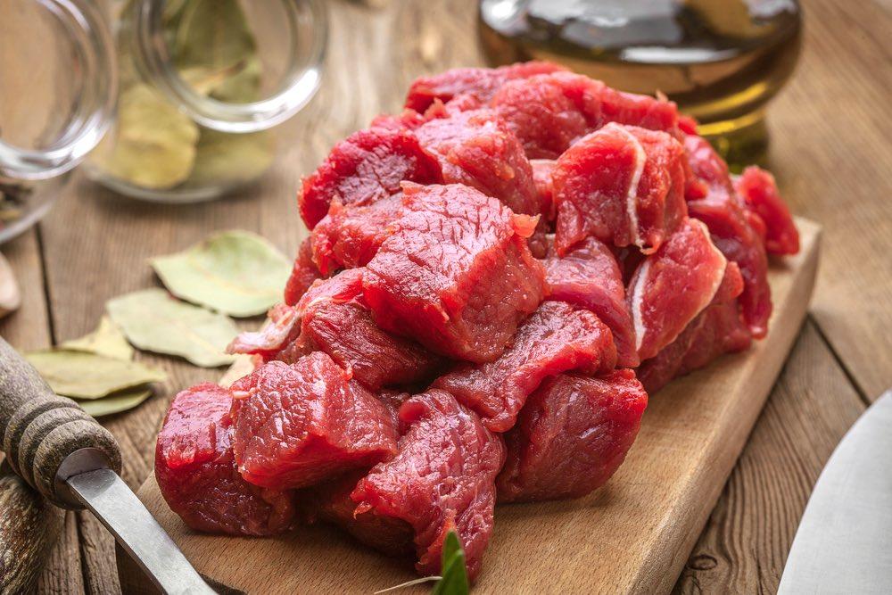 Carne di manzo o cinghiale tagliata a cubetti su un tagliere di legno