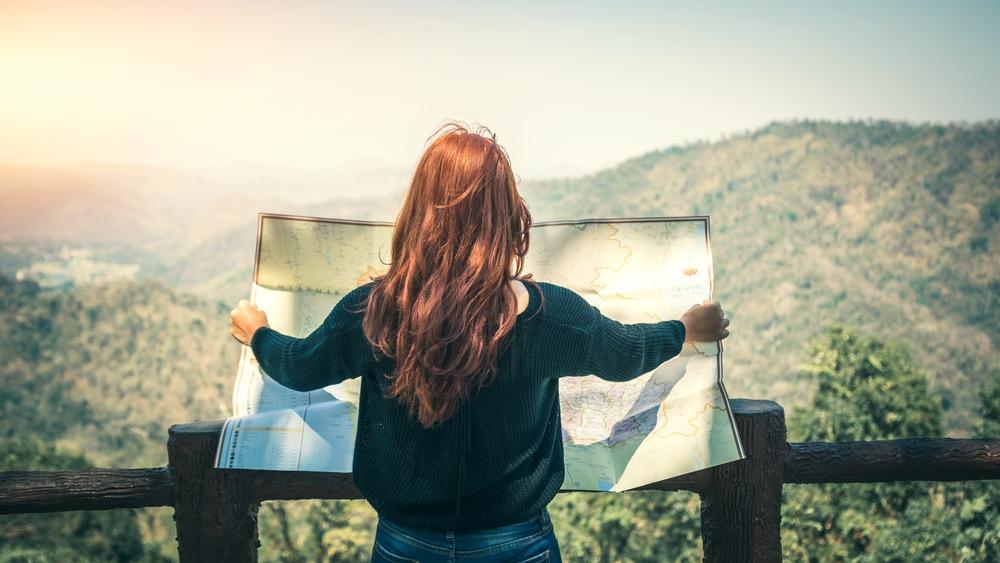 Ragazza guarda una mappa davanti a un panorama di montagna