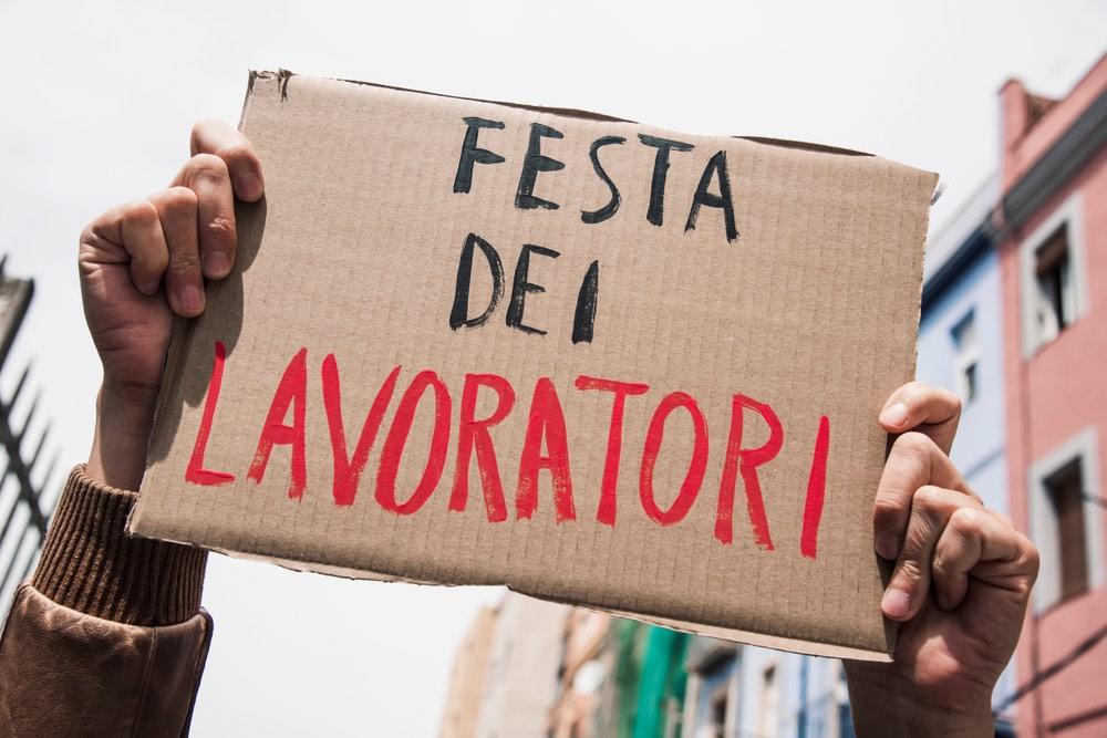 Cartello durante una manifestazione del 1° Maggio con la scritta Festa dei Lavoratori