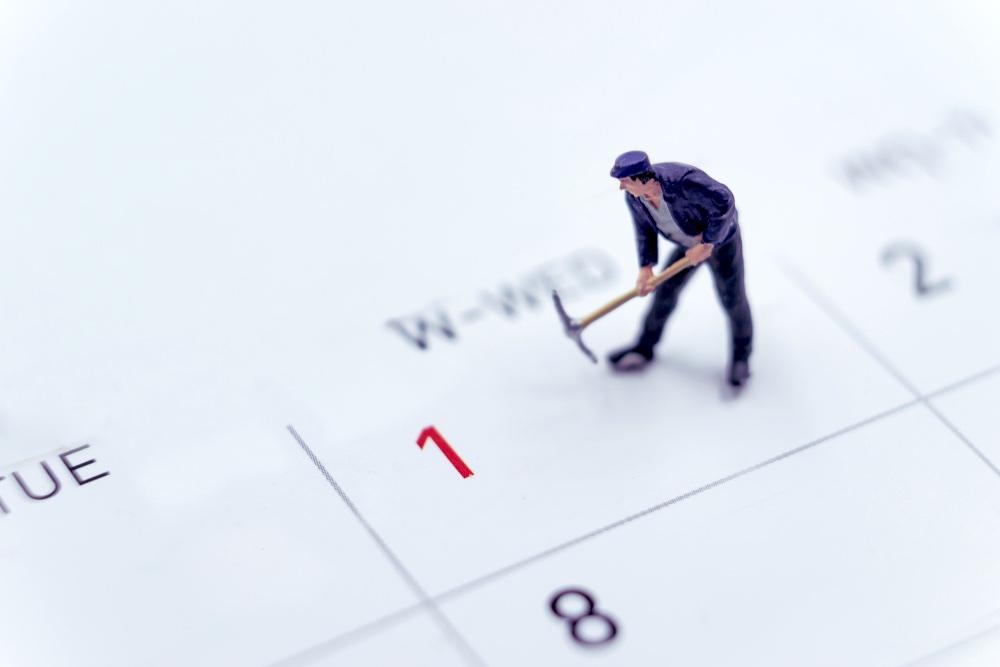 Miniatura di operaio su un calendario con evidenziata in rosso la data Primo Maggio, Festa dei Lavoratori