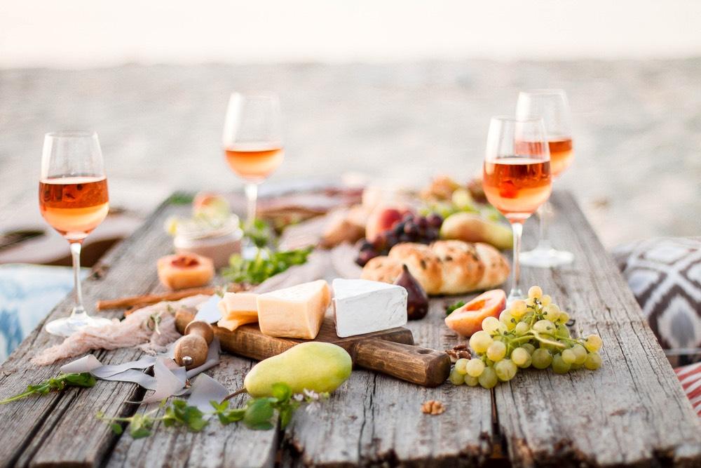 Bicchieri di orange wine, o vino macerato, su un tavolo di legno per un picnic sulla spiaggia