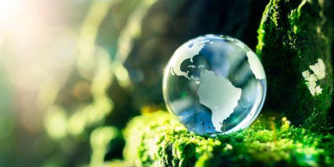 Pianeta di vetro in mezzo alla natura, concetto rivoluzione verde.
