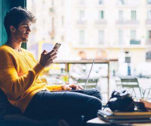 Un ragazzo in un bistrot lavora al computer e guarda il cellulare
