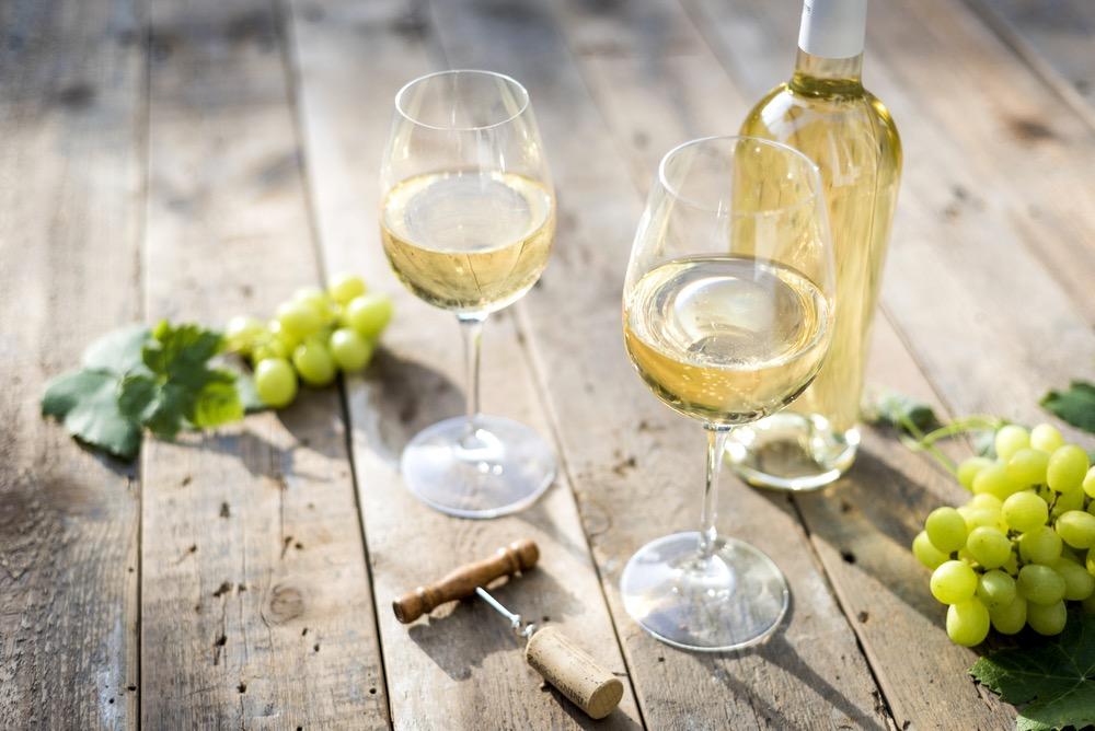 Bottiglia di trebbiano toscano su tavolo di legno insieme a grappoli d'uva