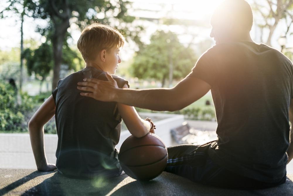 Un atleta di basket insieme al suo allenatore