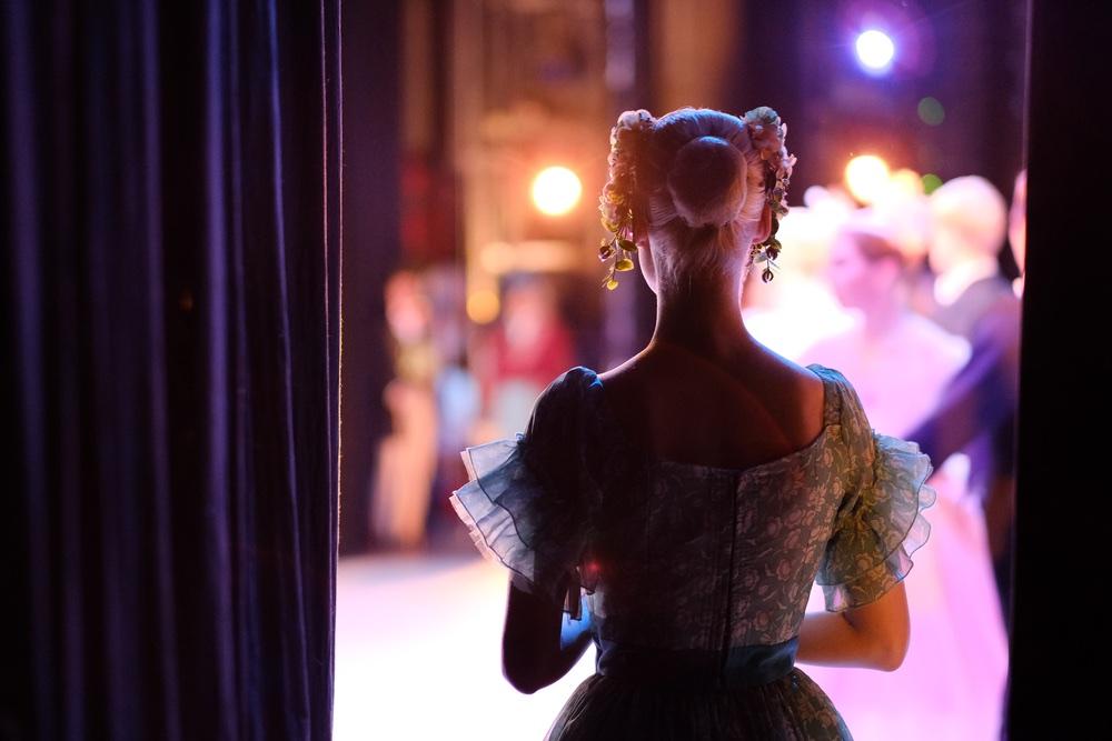 Un'attrice in attesa di entrare in scena dietro le quinte