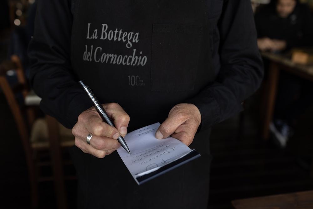 Cameriere prende una comanda alla trattoria in Mugello La Bottega del Cornocchio