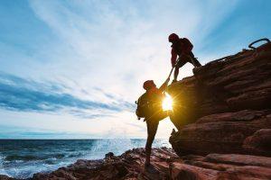 Una coppia di persone si aiutano a vicenda a scalare uno scogliera