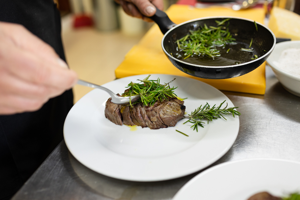 Chef impiatta un filetto di carne nella cucina della trattoria La Bottega del Cornocchio