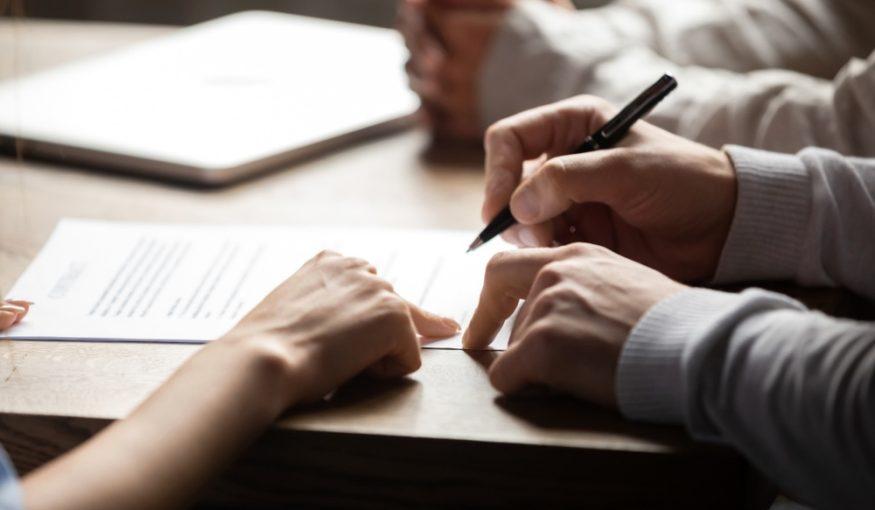 Persone firmano un contratto di vendita
