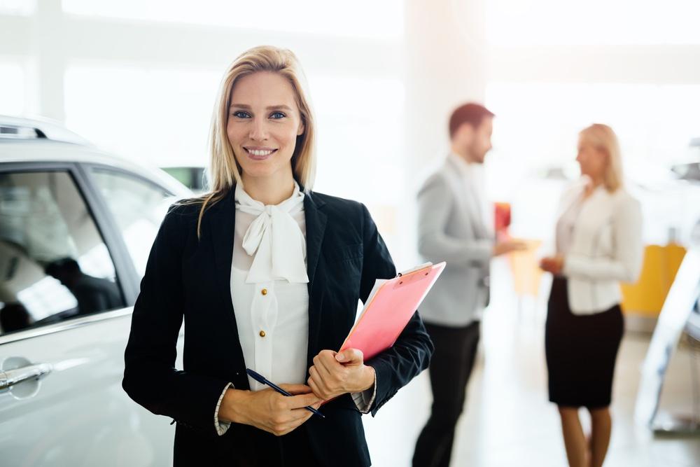 Venditrice di auto in una concessionaria con due clienti sullo sfondo