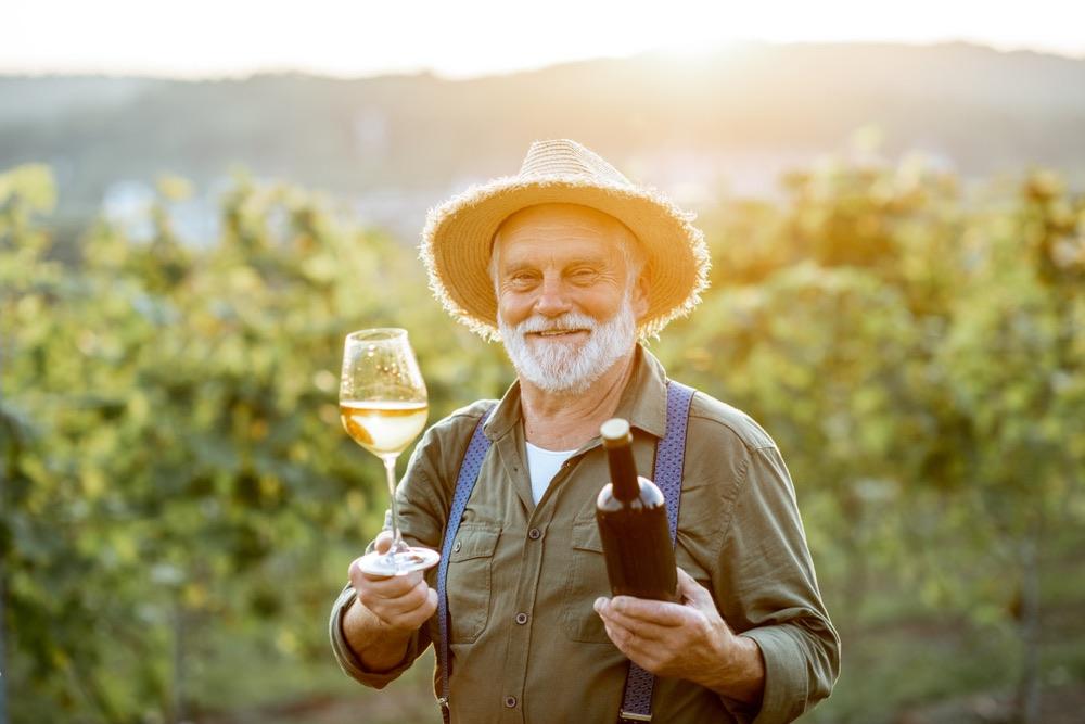 Anziano viticoltore in vigna con bicchiere e bottiglia di vino bianco