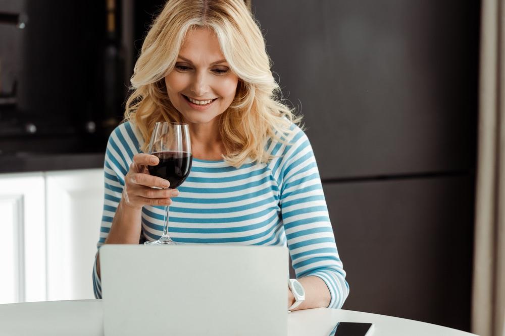 Una wine blogger con bicchiere di vino rosso davanti al pc