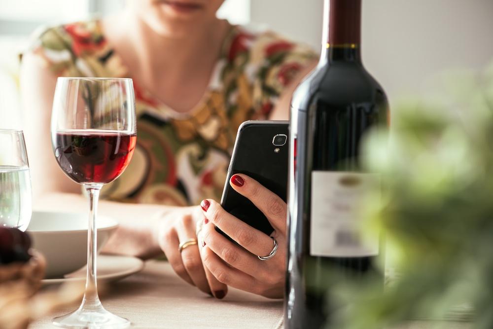 Ragazza utilizza telefono per fare foto a bottiglia di vino