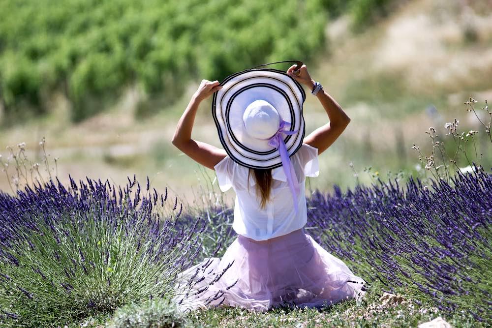 Ragazza con cappello in un campo di lavanda in Toscana nell'azienda Maremma