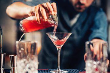 Barman versa in una coppa Martini un cocktail rosso