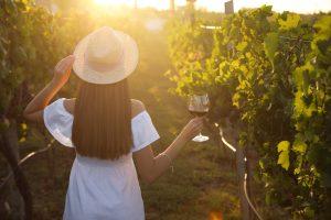 Giovane ragazza tra le vigne durante una degustazione di vino in Maremma