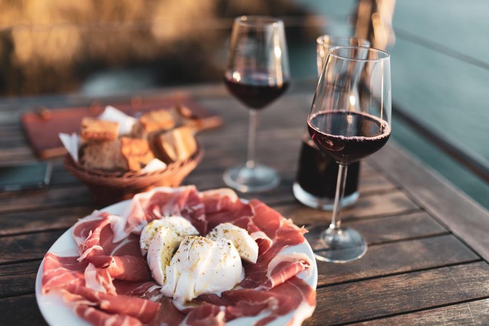 Tagliere di salumi e calici di vino sulla costa toscana