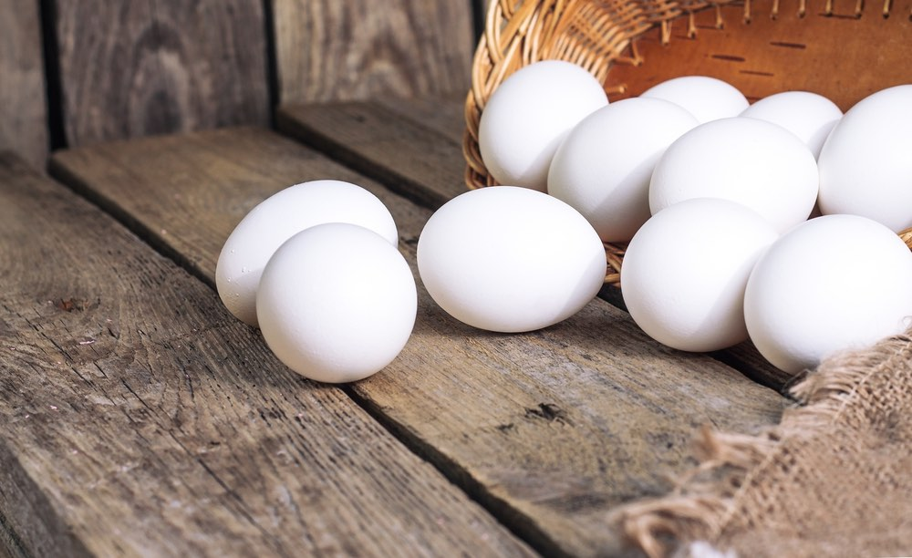 Uova di gallina bianche su tavolo di legno