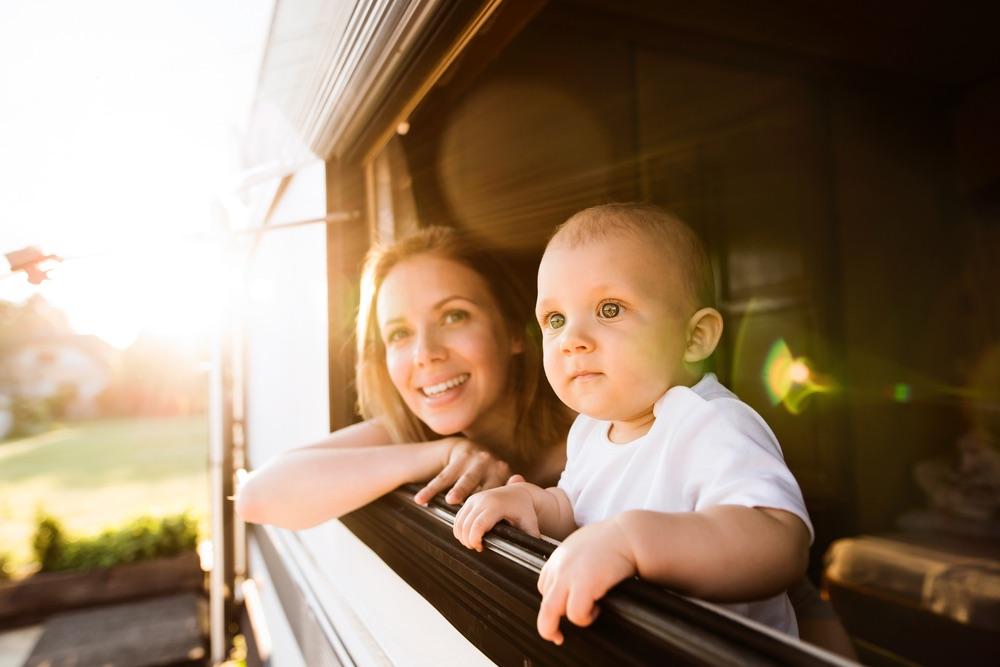 Mamma e bambino affacciati alla finestra del camper in vacanza in Toscana