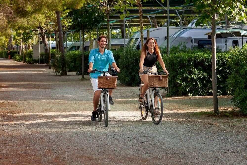 Ragazzo e ragazza in bici al Camping Village Pappasole, campeggio sul mare in Toscana