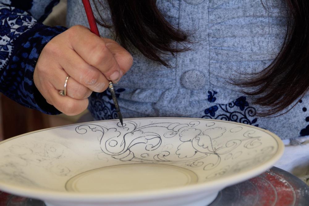 Artigiana decora piatto di ceramica Rampini a Radda in Chianti