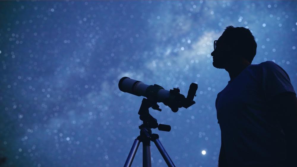 Un ragazzo guarda il cielo stellato con un telescopio a Stia in Toscana