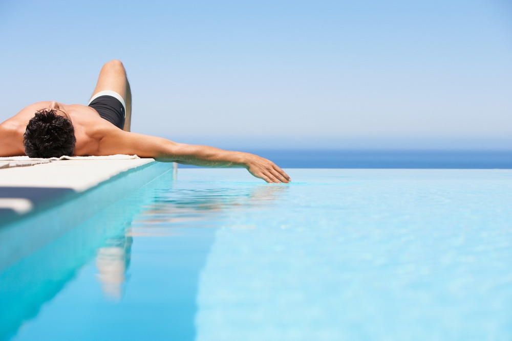 Ragazzo in costume si rilassa a bordo piscina con vista mare