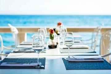 Tavolo apparecchiato in un ristorante vista mare in Toscana