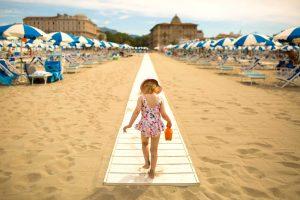 Graziosa bambina che cammina sulla passerella di un bagno di Viareggio