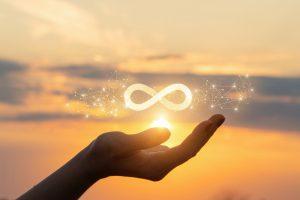 Il simbolo dell'infinito al tramonto su una mano