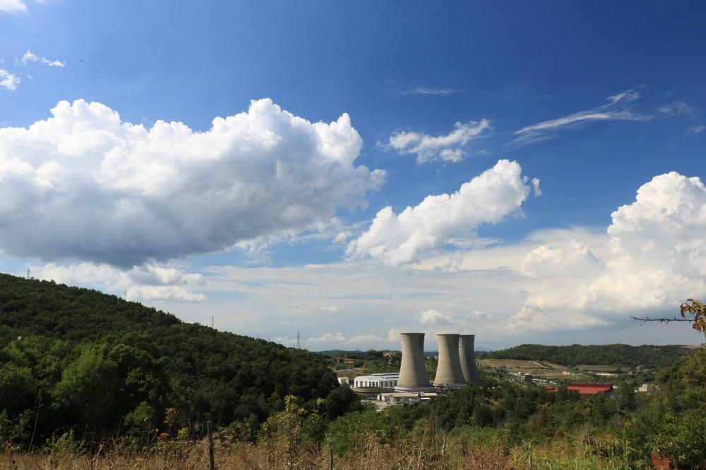 Centrale geotermica di Larderello sotto un cielo azzurro con nuvole bianche