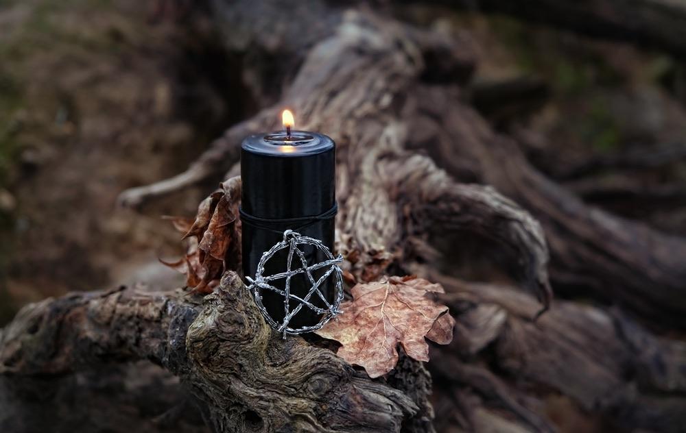 Candela nera accesa e stella a 5 punte in un bosco