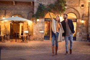 Coppia sorridente cammina per un borgo in Toscana la sera