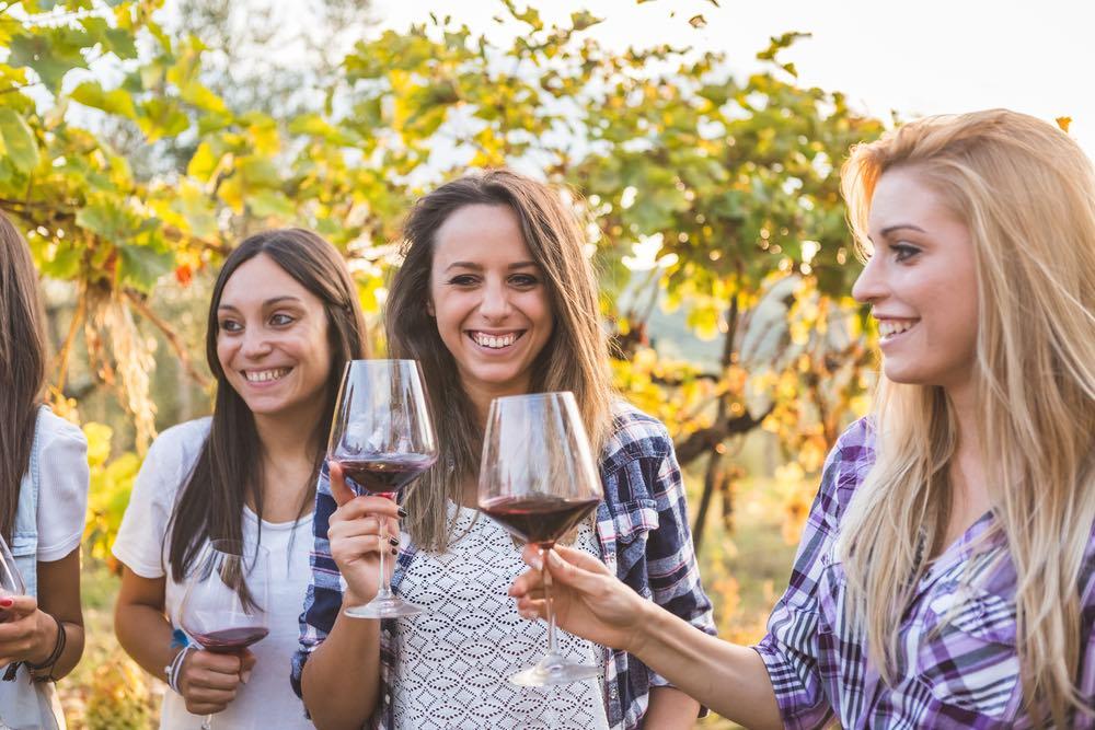 Amiche bevono vino rosso tra le vigne in Toscana